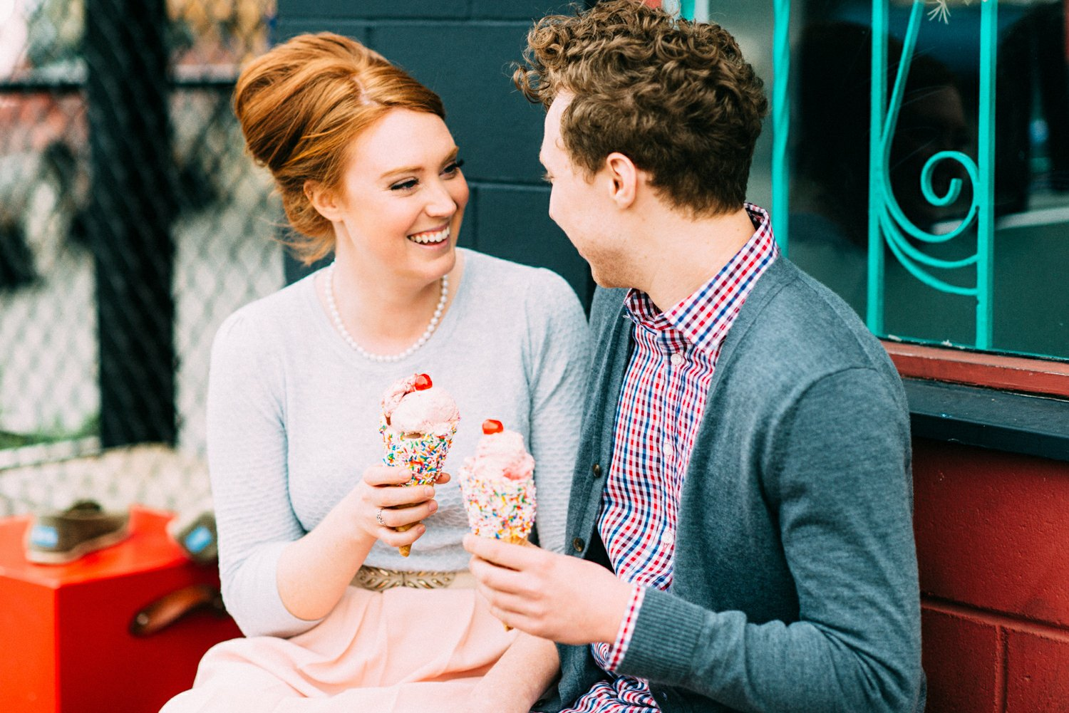 Couple laughs while eating ice cream during their fifties styled engagement shoot