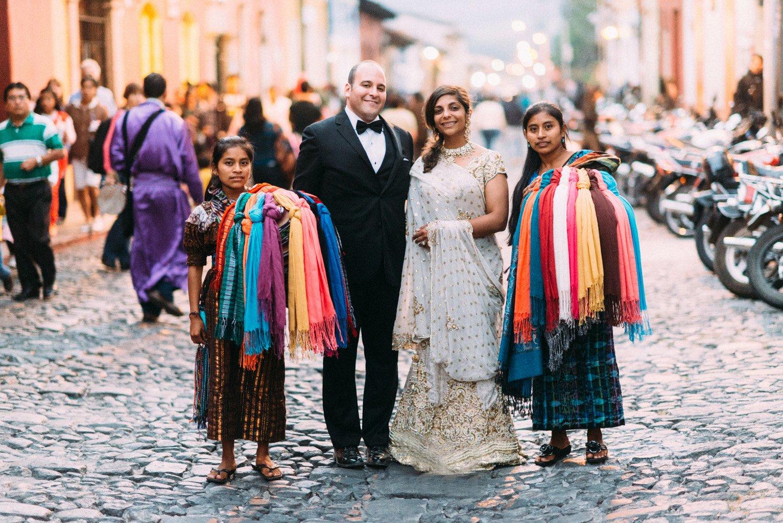 Bride and groom in Antigua Guatemala standing next to Mayan women.