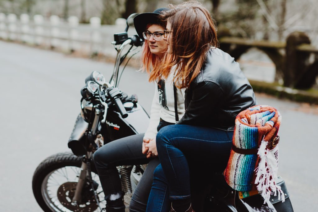 Lesbian couple sit on harley after their elopement at Multnomah Falls Portland Oregon