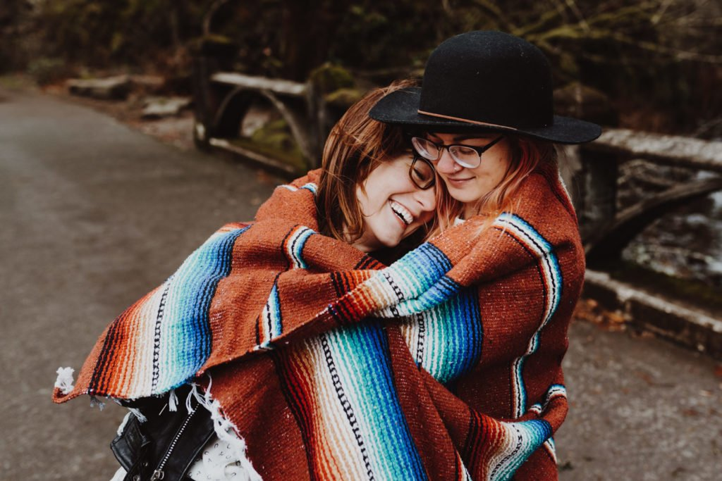 Lesbian couple embrace during their elopement at Multnomah Falls Portland Oregon