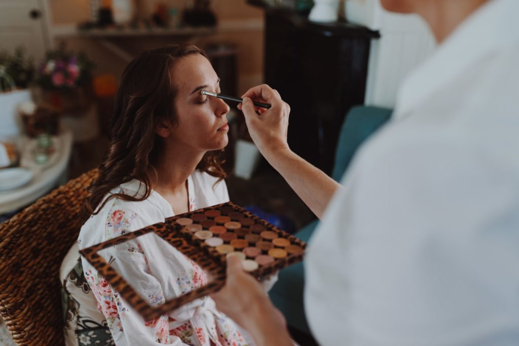 Makeup artist applying brides makeup before wedding
