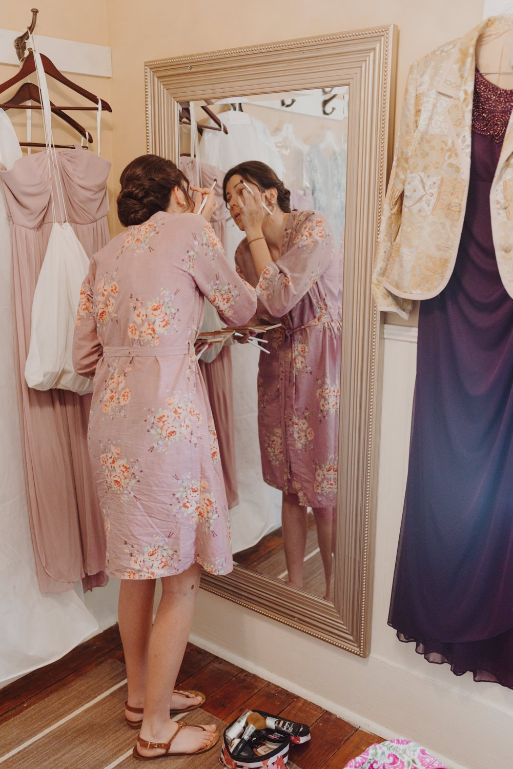 Bridesmaid applying makeup before wedding ceremony