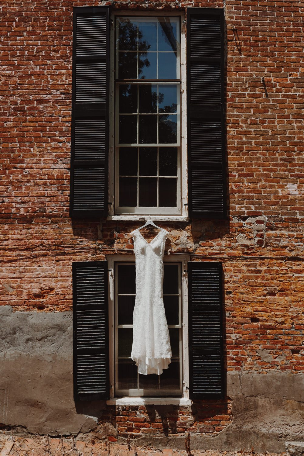 brides wedding dress hanging on brick wall