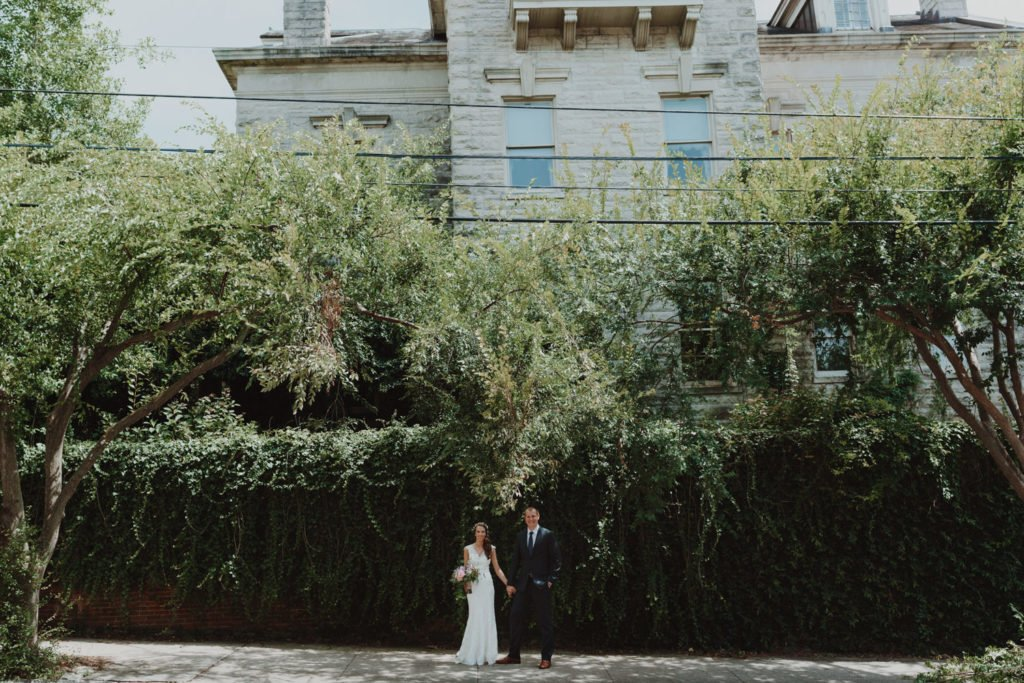 Wide shot of bride and groom near ivy wall