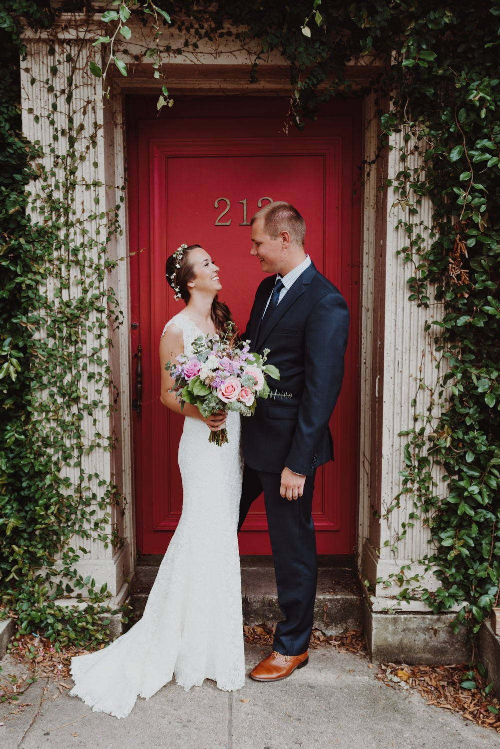 Boho bride and groom in front of red door