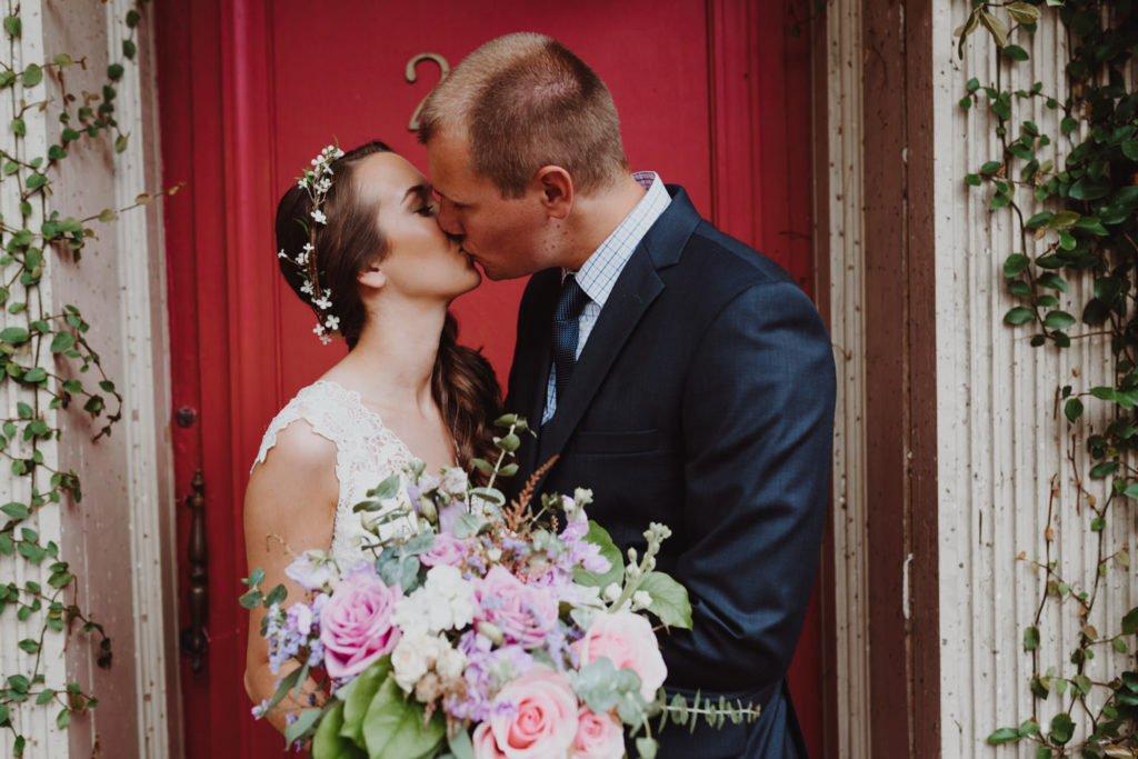 Boho bride and groom in front of red door