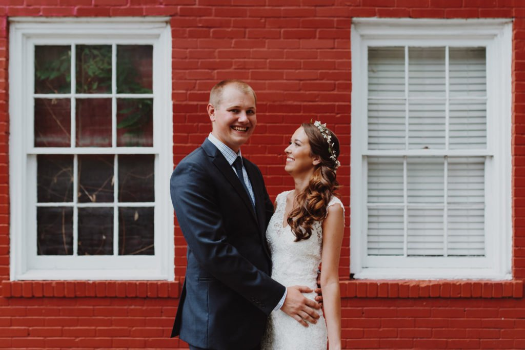 Boho bride and groom in front of red wall