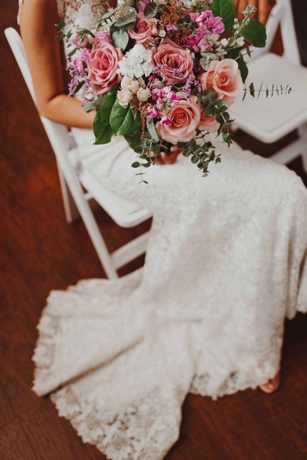 Bride sits in church before wedding ceremony with her bouquet