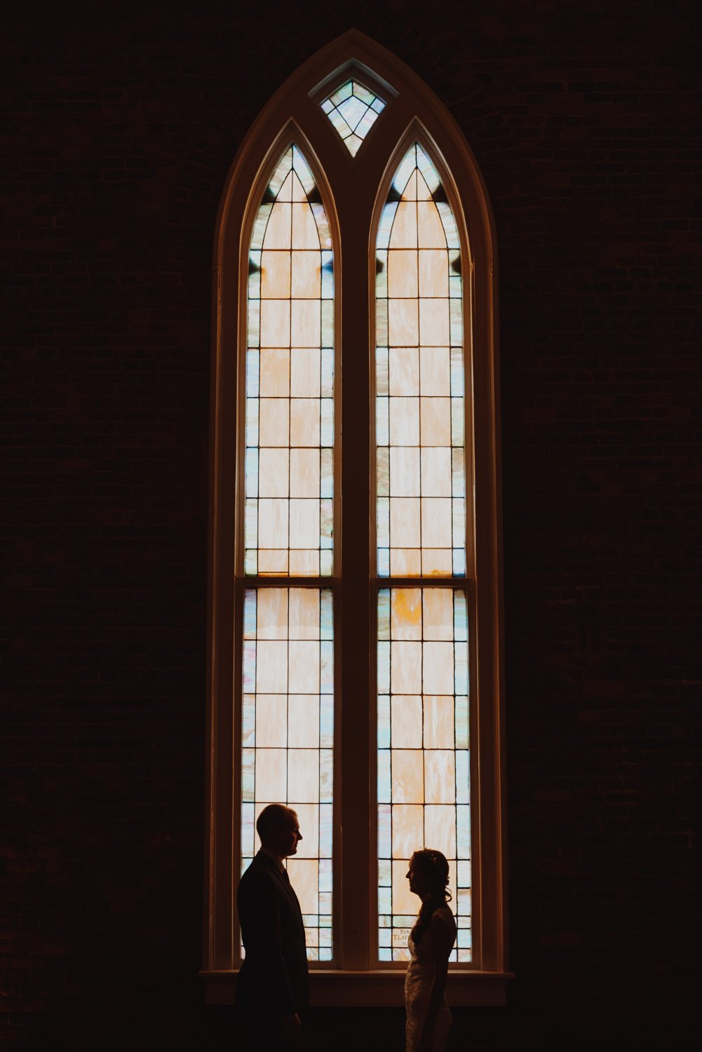 Bride and groom stand silhouetted in front of Portland Oregon church windows
