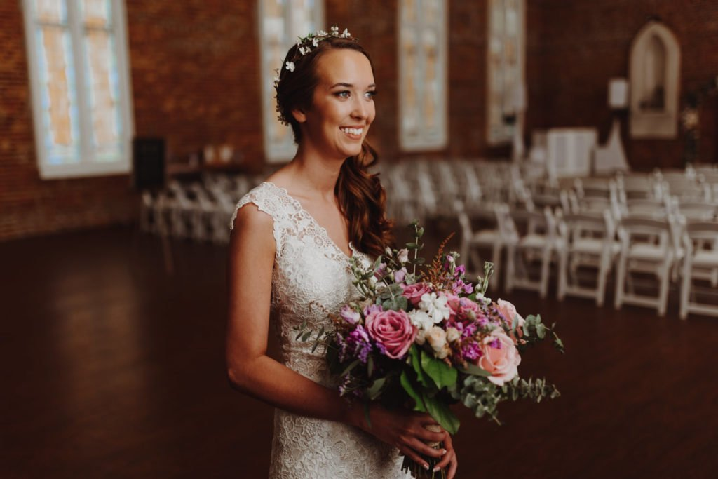 Boho bride smiles in church holding bouquet before her wedding ceremony