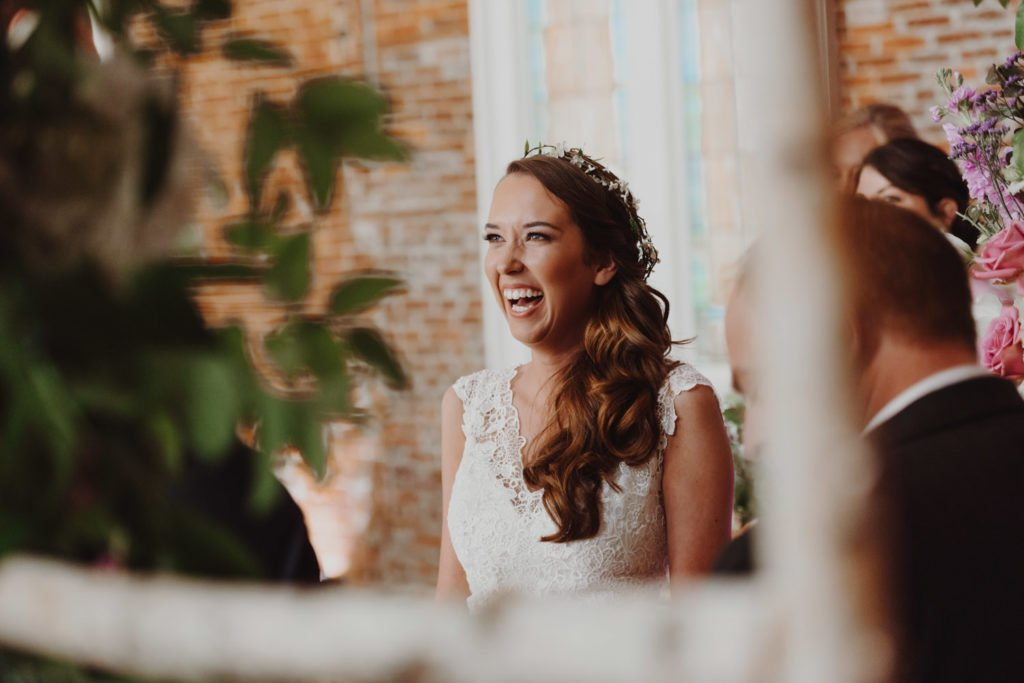 Boho brride laughs during her downtown Portland Oregon wedding ceremony