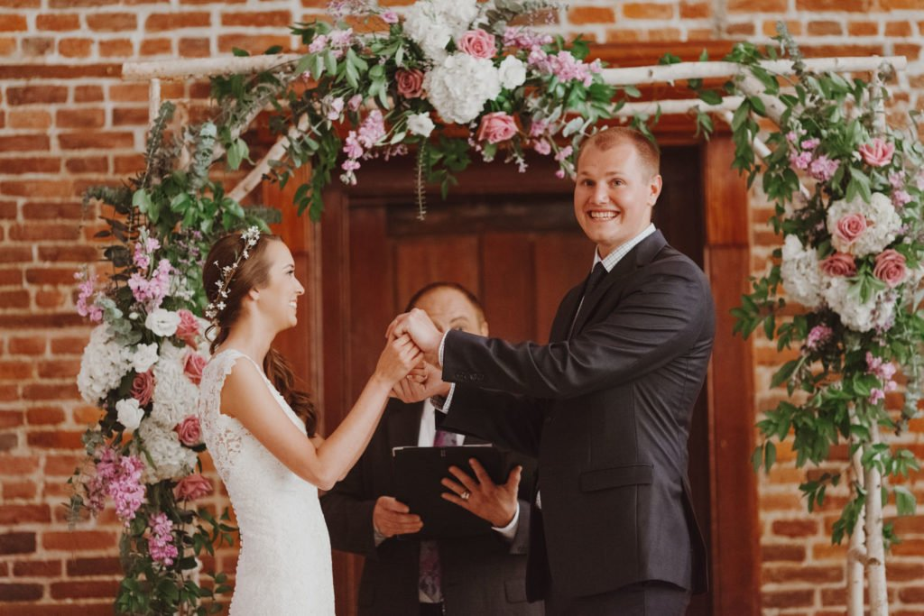 Groom smiles as he puts ring on bride's finger