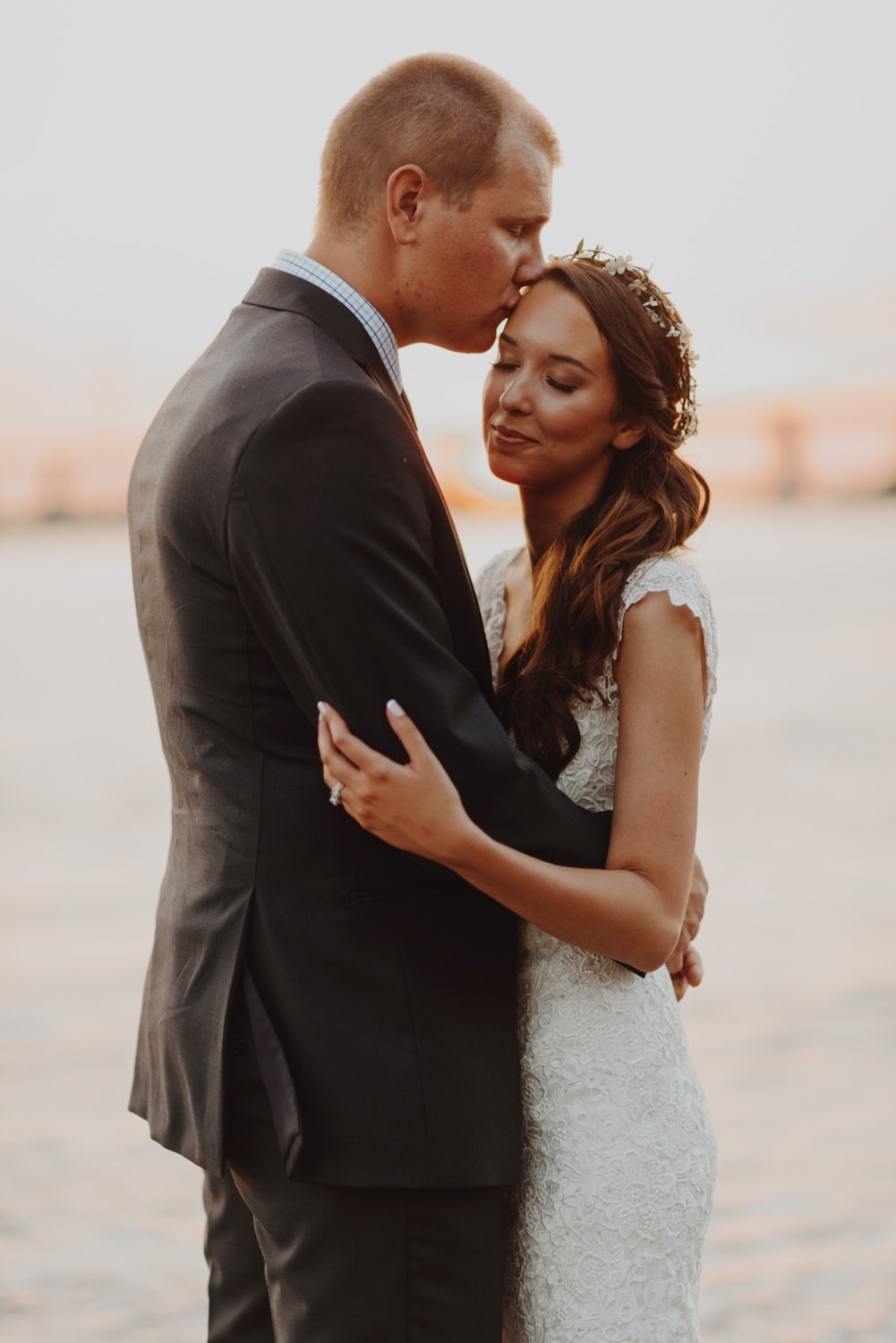 Bride and groom kiss on the shores of the Willamette River in downtown Portland Oregon