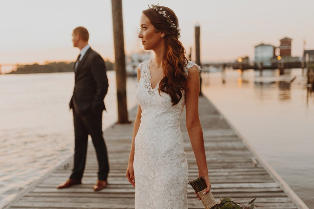 Bride and groom look off to the sunset on the shores of the Willamette River in downtown Portland Oregon