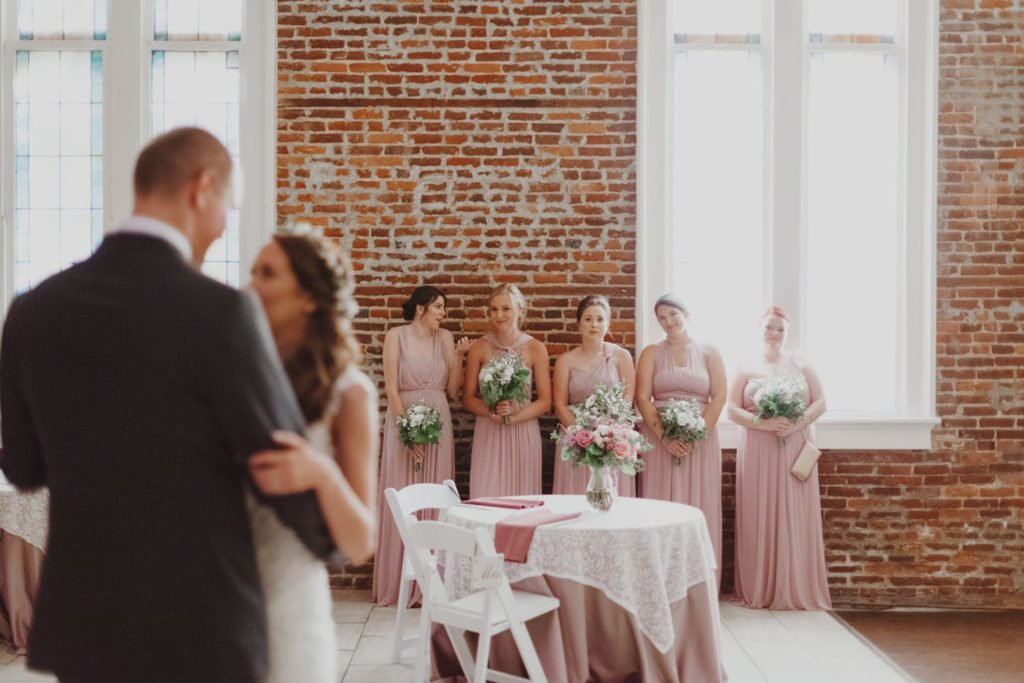 Bridesmaids watch bride and groom first dance in exposed brick building