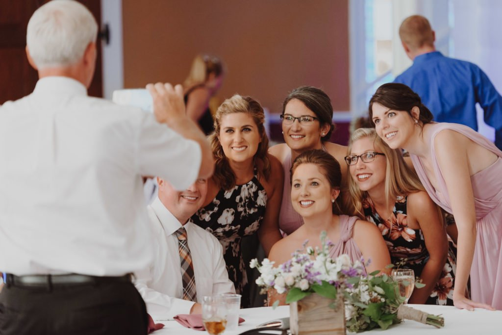 Table at wedding takes a group selfie photo