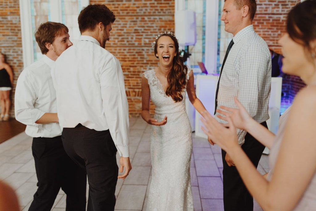 Bride laughs on the dance floor of an exposed brick building in downtown Portland Oregon