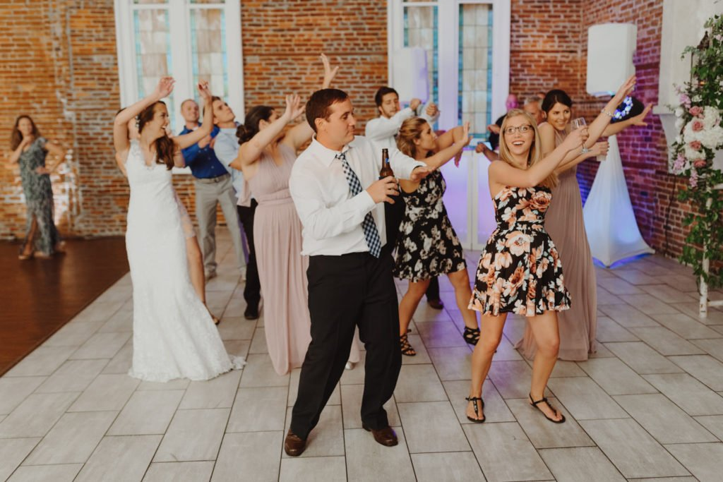 Bride dances on the dance floor of an exposed brick building in downtown Portland Oregon