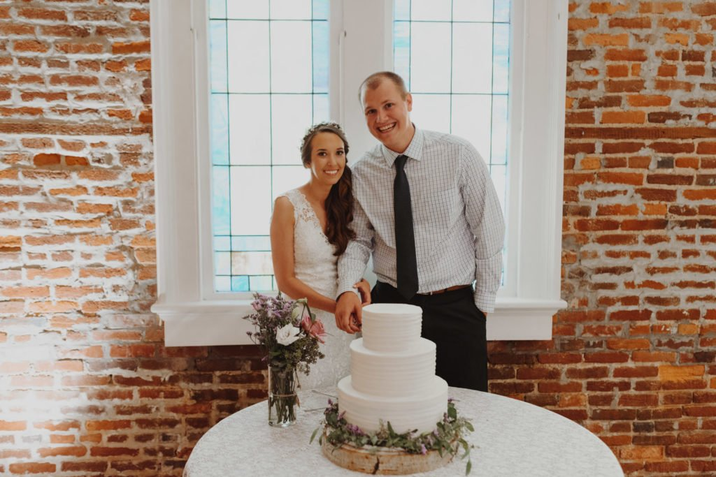 Bride and groom cut cake on an exposed brick building in downtown Portland Oregon