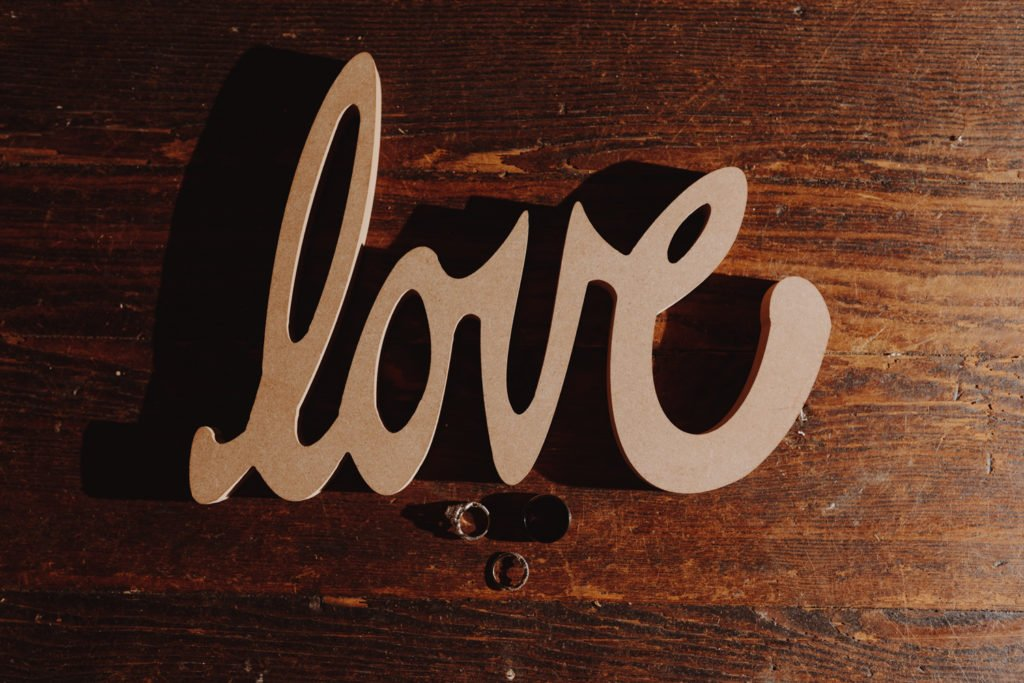 "Wedding ring shot next to a ""Love"" sign on a wooden floor"