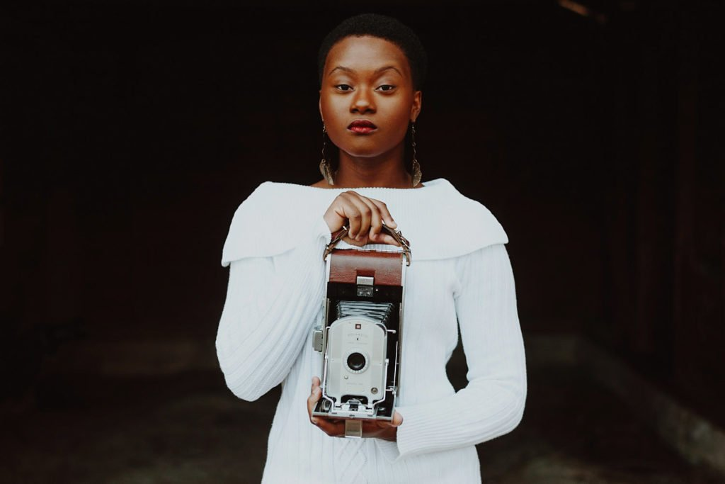African American model stands holding vintage camera at Mark Maya's Workshop in Durham NC