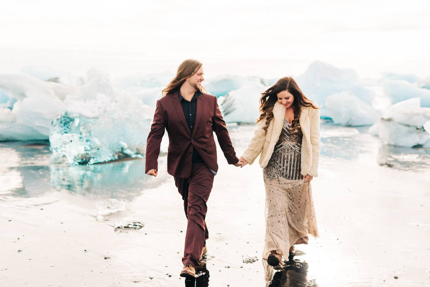 trendy Iceland Elopement Bride and Groom on black sand beach